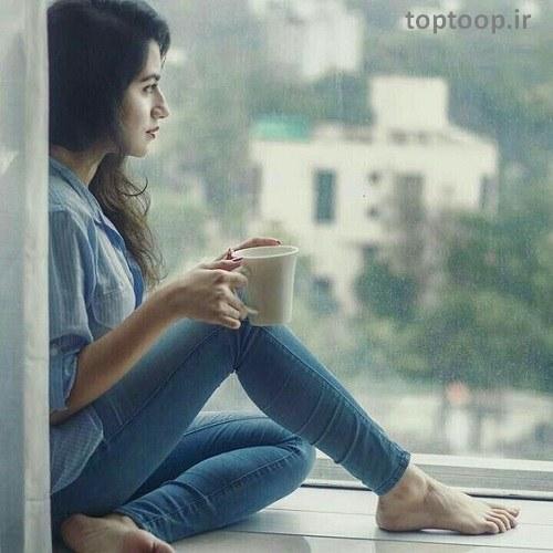 دختر خیلی غمگینی که دم پنجره نشسته و استکان قهوه دستش هست مناسب پروفایل