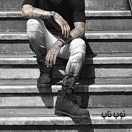پسری با دست های خالکوبی شده روی پله ها نشسته