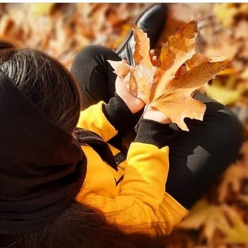 پروفایل دخترونه با لباس زرد پاییزی برگ در دست