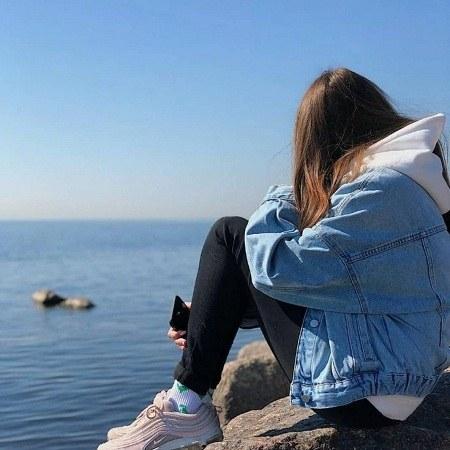 پروفایل دختر تنها و غمگین کنار دریا نشسته